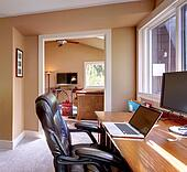 Home office and computer and chair with brown walls.