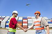 two happy workers handshaking before transportation containers