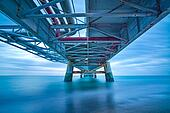 Industrial pier on the sea. Bottom view. Long exposure photography.