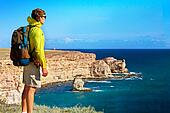 Man Traveler with backpack relaxing outdoor with Sea and Rocks coastal on background Freedom and Healthy Lifestyle concept